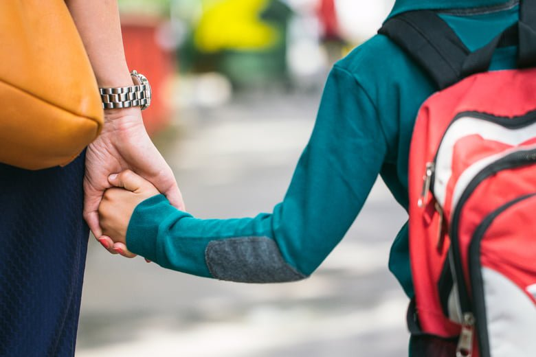 Child holding his mum's hand on the way to school