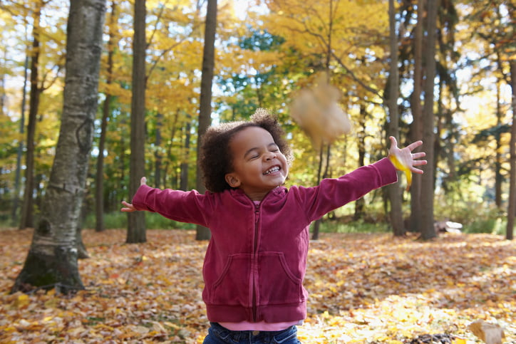 A young girl playing in a forest in autumn